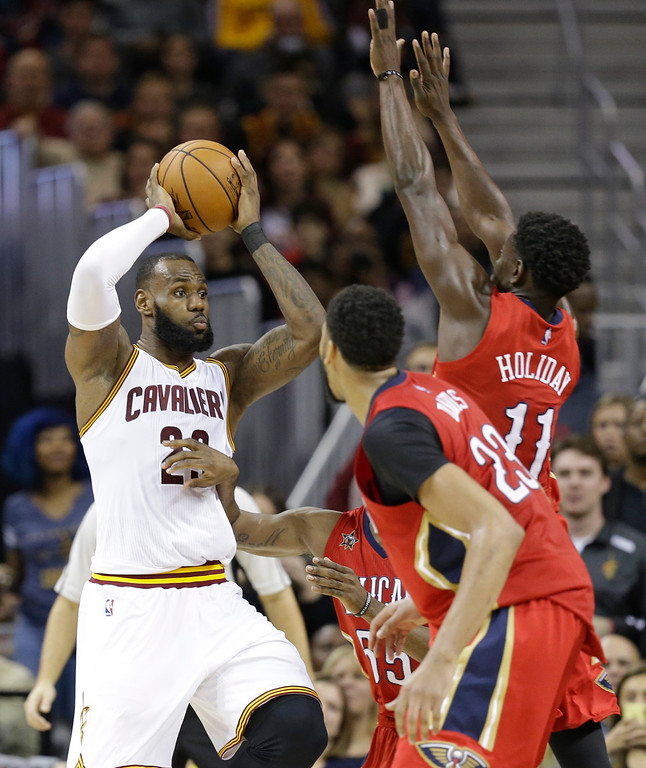 . Cleveland Cavaliers\' LeBron James, left, passes against the New Orleans Pelicans in the second half of an NBA basketball game, Monday, Jan. 2, 2017, in Cleveland. (AP Photo/Tony Dejak)