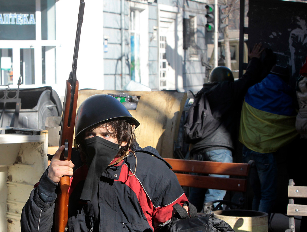 . Anti-government protesters take cover behind a barricade during clashes with riot police outside Ukraine\'s parliament in Kiev, Ukraine, Tuesday, Feb. 18, 2014.  (AP Photo/Sergei Chuzavkov)