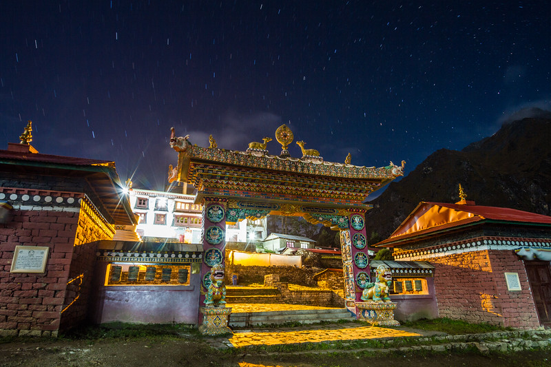 The Buddhist monastery at Tangboche is seen at night with Himalayan peaks behind it.