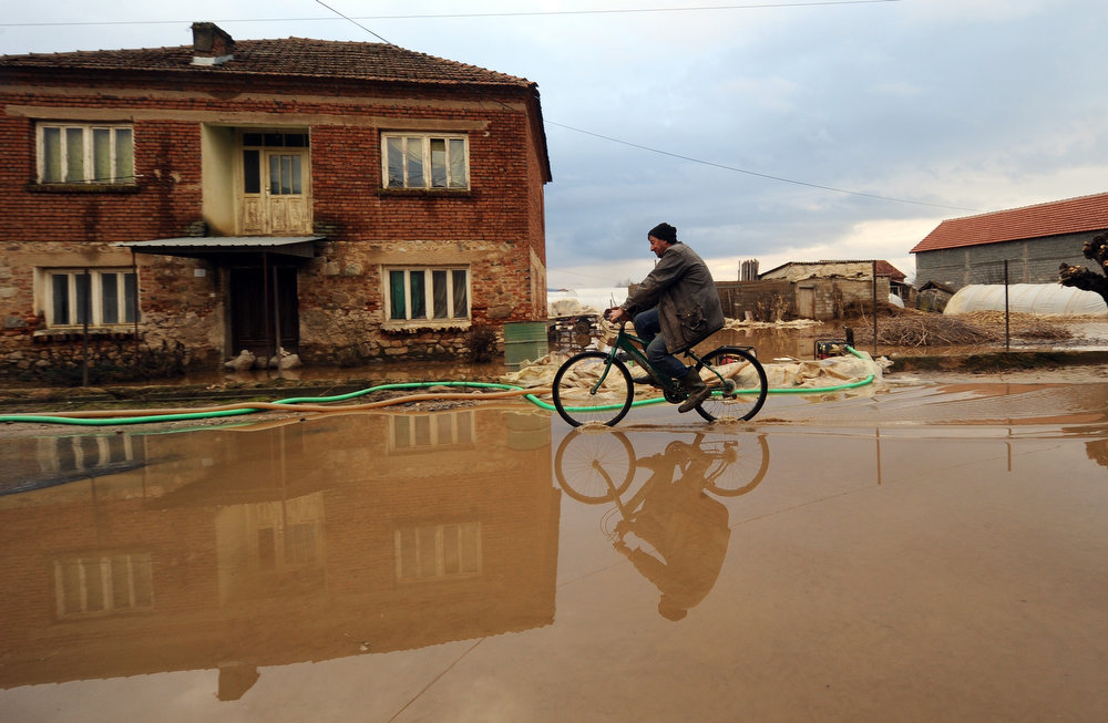 Description of . A man cycles through a flooded alley in the village of Murtino, in the southeastern tip of the Republic of Macedonia on February 27, 2013. The torrential rains which in the last three days poured down on the fertile Strumica Valley inundated fields and villages, destroying or damaging crops and households. Tens of people in the region are now sheltered, as their homes were gravely damaged. ROBERT ATANASOVSKI/AFP/Getty Images