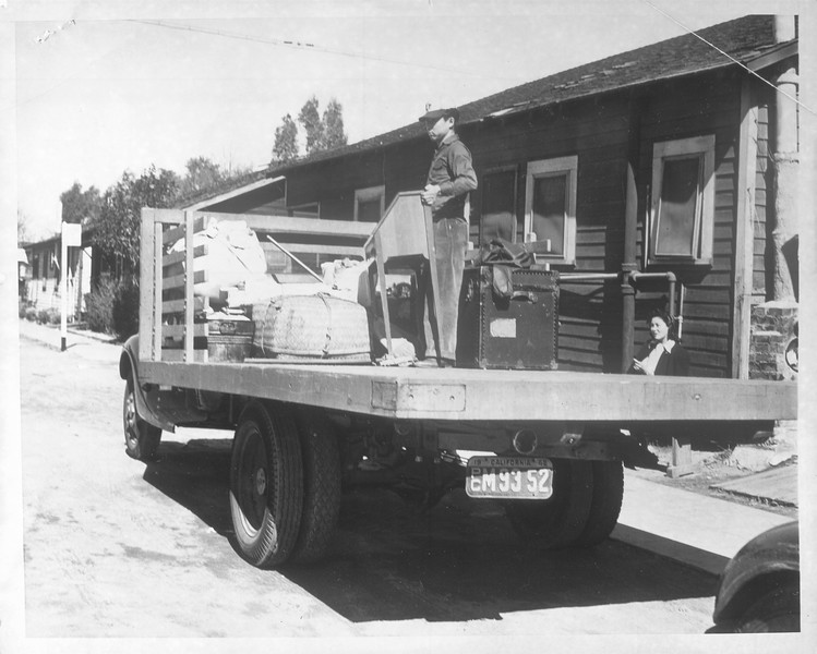 """""""Y. Yats, Japanese boy helps his neighbor, Mrs. T. Oki at 109 Cannery St., Terminal Island load her belongings aboard truck.""""--caption on photograph"""