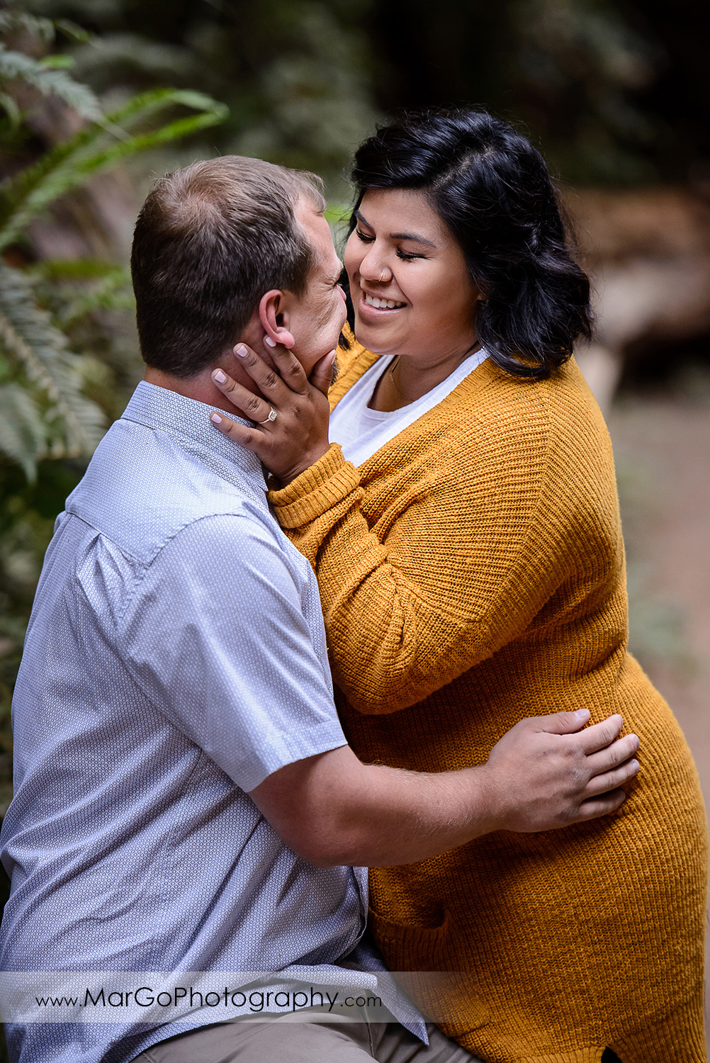 engaged couple kissing at Muir Woods National Monument