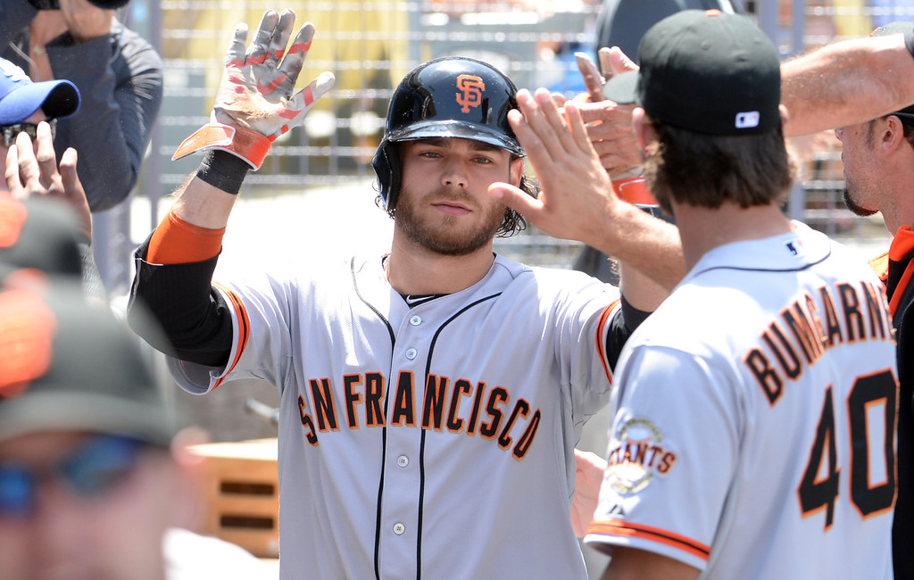 . San Francisco Giants\' Brandon Crawford high fives teammates after scoring on a Hunter Pence sac fly ball in the second inning of a Major league baseball game against the Los Angeles Dodgers on Saturday, May 10, 2013 in Los Angeles.   (Keith Birmingham/Pasadena Star-News)