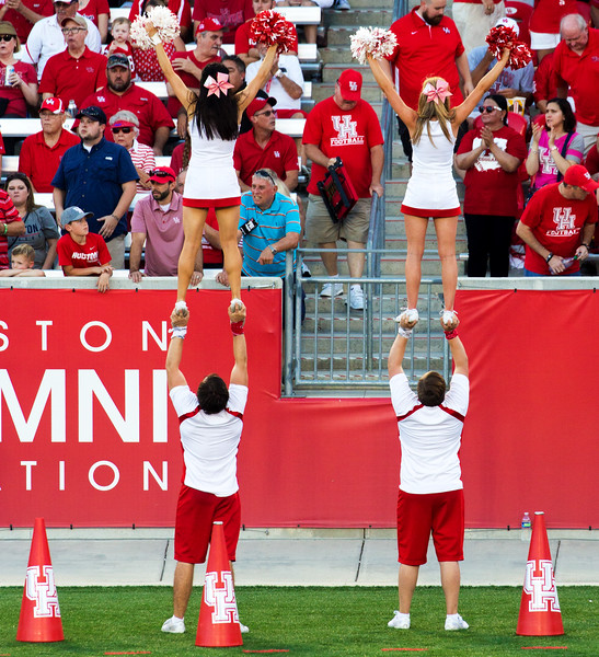 Across the field: Cheerleaders doing their balancing act