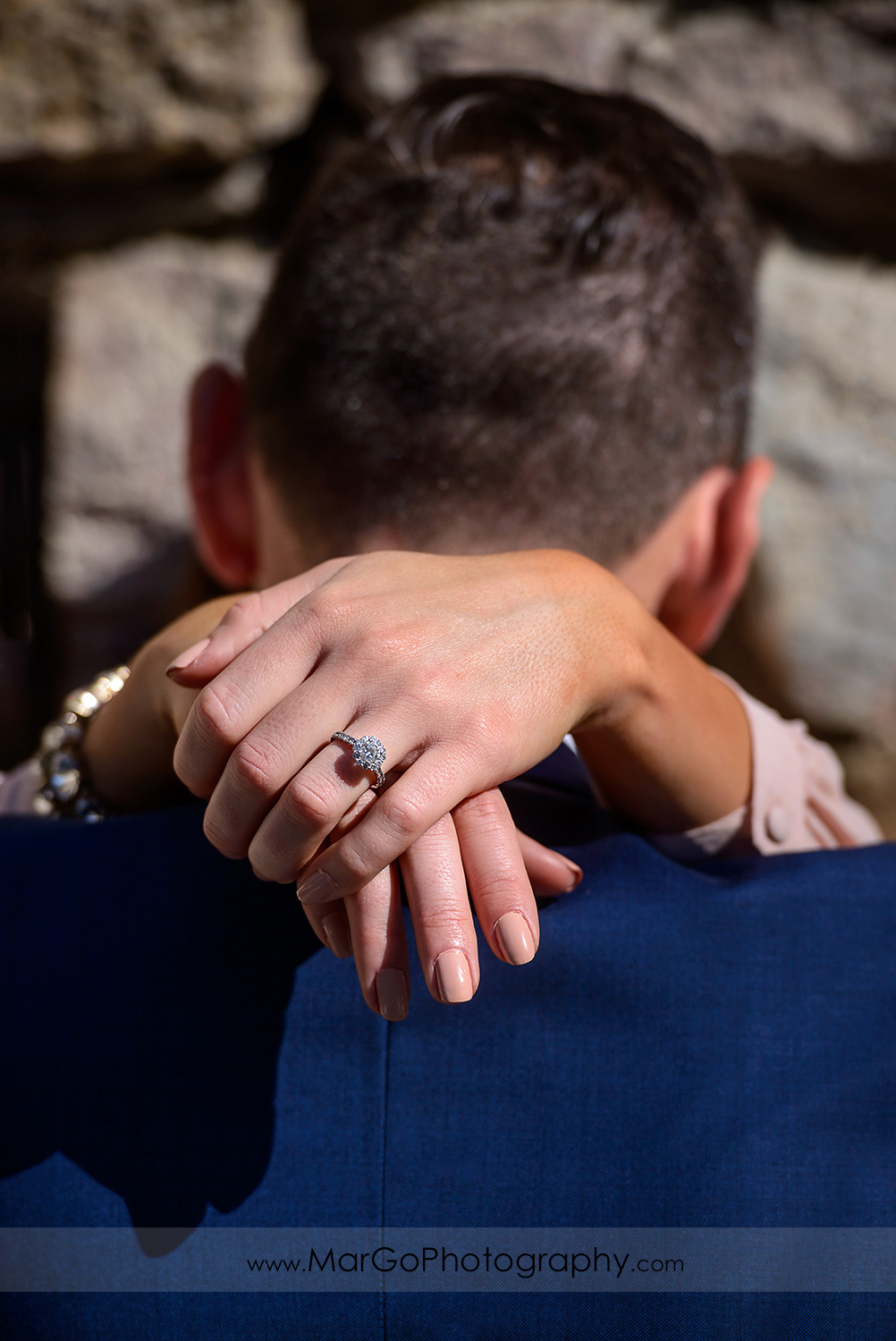 ring shot of woman in pink dress and man in blue suit during Napa Valley engagement session at Castello di Amorosa in Calistoga