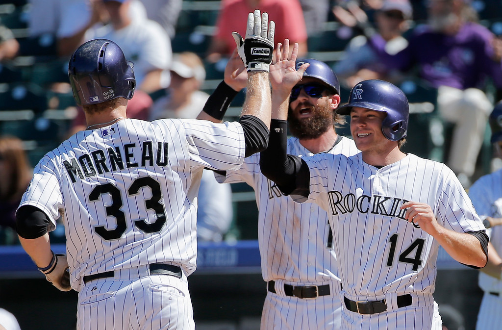 . DENVER, CO - SEPTEMBER 17:  Justin Morneau #33 of the Colorado Rockies celebrates his three run home run off of Carlos Frias #77 of the Los Angeles Dodgers with Josh Rutledge #14 and Charlie Blackmon #19 of the Colorado Rockies to give the Rockies a 3-0 lead in the first inning at Coors Field on September 17, 2014 in Denver, Colorado.  (Photo by Doug Pensinger/Getty Images)