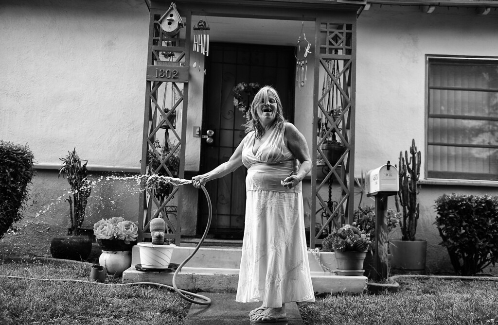 . Dorothy waters her collection of cacti and succulents on her front porch.