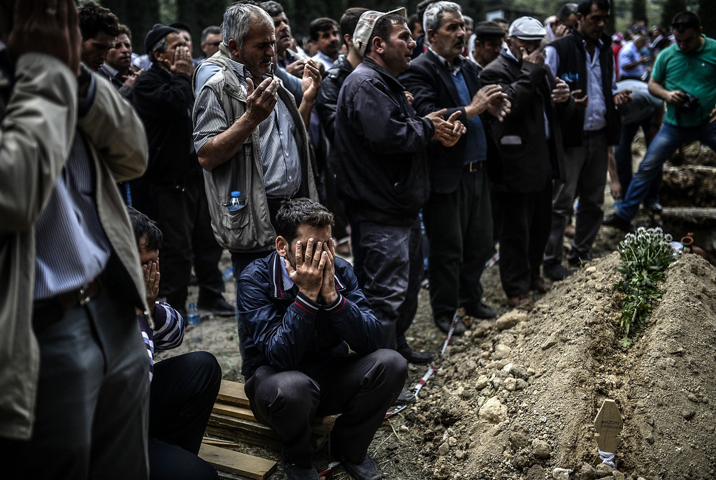 . People mourn near graves during a funeral ceremony in the western town of Soma in the Manisa province, on May 15, 2014. Turkey\'s four biggest unions will hold a one-day protest strike as anger over the country\'s worst mining accident mounts, with 282 workers confirmed dead and scores still trapped underground. AFP PHOTO/BULENT KILIC/AFP/Getty Images