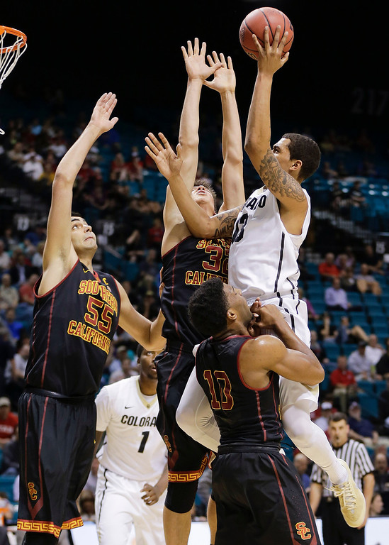 . Southern California\'s Pe\'Shon Howard (10) draws an offensive foul on Colorado\'s Dustin Thomas, right, as USC\'s Omar Oraby (55) and Nikola Jovanovic (32) help defend in the first half of an NCAA college basketball game in the Pac-12 men\'s tournament, Wednesday, March 12, 2014, in Las Vegas. (AP Photo/Julie Jacobson)