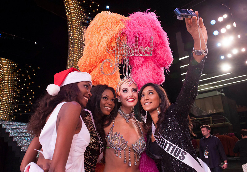 . Miss Haiti 2012 Christela Jacques (L), Miss Gabon 2012 Channa Divouvi and Miss Mauritius 2012 Ameeksha Dilchand (R) pose for a photo with performer Chantell Adams from the Jubilee Show at Bally\'s in Las Vegas, Nevada December 6, 2012. The Miss Universe 2012 competition will be held on December 19. REUTERS/Valerie Macon/Miss Universe Organization L.P/Handout