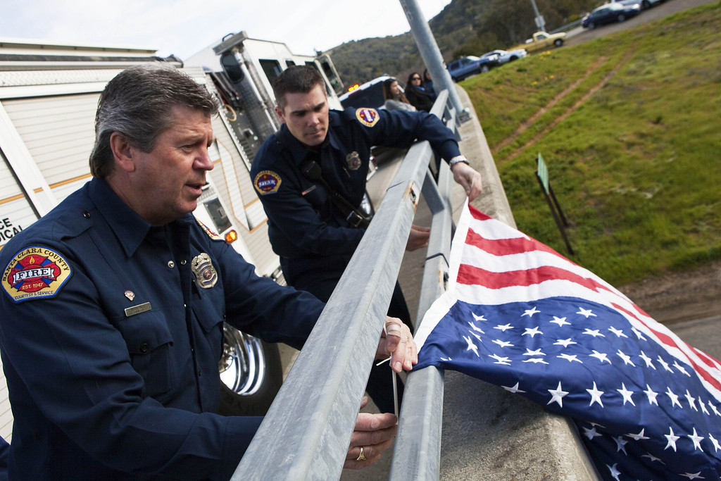 . Santa Clara firefighters Bruce Ingle (L), and David Sosine attach a flag to an overpass in preparation for the motorcade as a procession honoring Santa Cruz Police Department officers Loran Baker and Elizabeth Butler travels to the officers\' memorial services in San Jose, California March 7, 2013. The two officers were killed in the line of duty February 26 while arriving at the home of a suspect they were to question.  REUTERS/Mark Avery  (UNITED STATES - Tags: CRIME LAW)