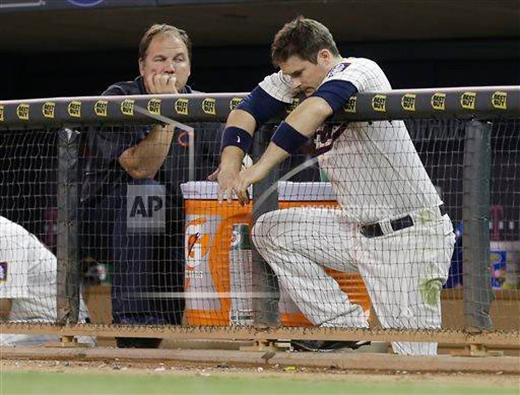. Minnesota Twins\' Josh Willingham hangs his arms over the dugout fence in the ninth inning. At left is head trainer Dave Pruemer. (AP Photo/Jim Mone)