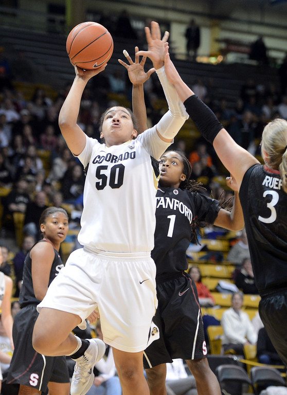 . Jamee Swan of CU gets past Alex Green of Stanford during the first half of the January 12, 2014 game in Boulder. Cliff Grassmick/Daily Camera