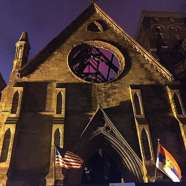 150+ year old church burned to nearly nothing last week on 25th St. The red through what used to be a stained glass window is the reflection of the Empire State Building lit in red.