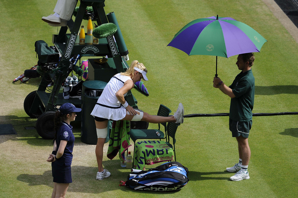 . Poland\'s Agnieszka Radwanska checks her strapping in their women\'s singles semi-final match against Germany\'s Sabine Lisicki on day ten of the 2013 Wimbledon Championships tennis tournament at the All England Club in Wimbledon, southwest London, on July 4, 2013. Lisicki won 6-4, 2-6, 9-7. TOM HEVEZI/AFP/Getty Images