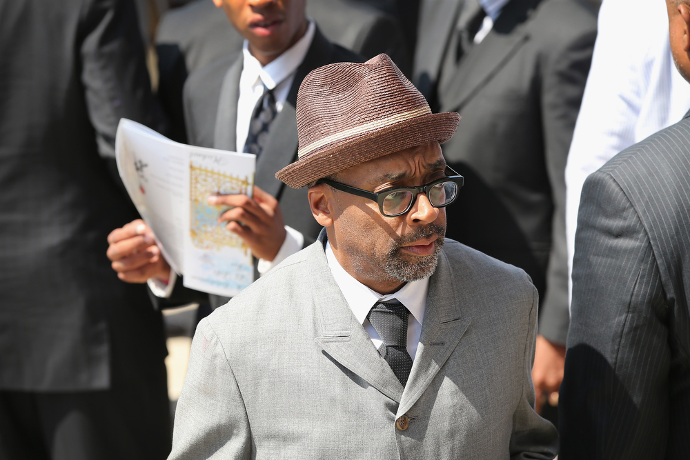 Description of . Filmmaker Spike Lee waits for the remains of Michael Brown to be loaded into a hearse following his funeral services at   the Friendly Temple Missionary Baptist Church on August 25, 2014 in St. Louis, Missouri. Michael Brown, an 18 year-old unarmed teenager, was shot and killed by Ferguson Police Officer Darren Wilson in the nearby town of Ferguson, Missouri on August 9. His death caused several days of violent protests along with rioting and looting in Ferguson.  (Photo by Scott Olson/Getty Images)