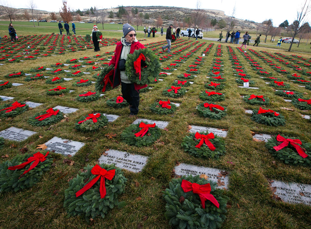 """. Margot McFarland of Boise helps lay wreaths on veterans\' grave sites Saturday, Dec. 13, 2014, at the Idaho State Veterans Cemetery. \""""It touches my heart to honor those who protect our freedom,\"""" McFarland said. \""""I hope someone is doing this for veterans in my family back in Indiana.\"""" The Boise Civil Air Patrol coordinated the annual Wreaths Across America event with volunteers who laid 3,100 wreaths. (AP Photo/The Idaho Statesman, Darin Oswald )"""