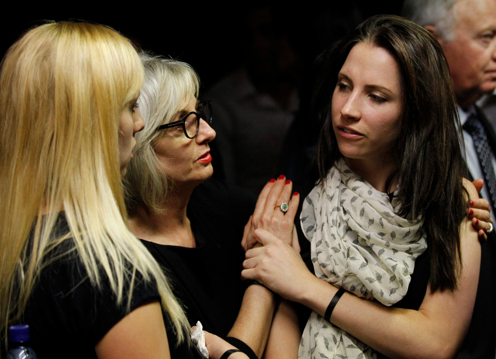 Description of . Oscar Pistorius's sister Aimee (R) reacts as she is consoled by relatives at the end of her brother's court appearance in the Pretoria Magistrates court February 19, 2013. Pistorius, a double amputee who became one of the biggest names in world athletics, was applying for bail aftr being charged in court with shooting dead his girlfriend, 30-year-old model Reeva Steenkamp, in his Pretoria house. REUTERS/Siphiwe Sibeko