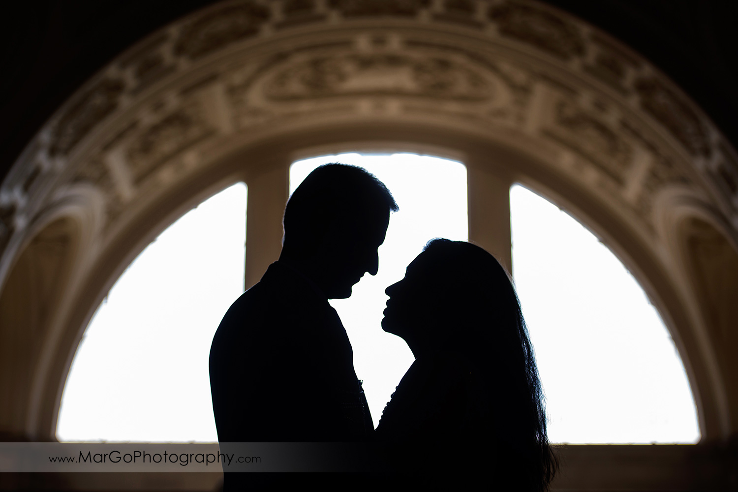 silhouette of man and woman lokking at each otherin front od big arch window on the fourth floor of San Francisco City Hall