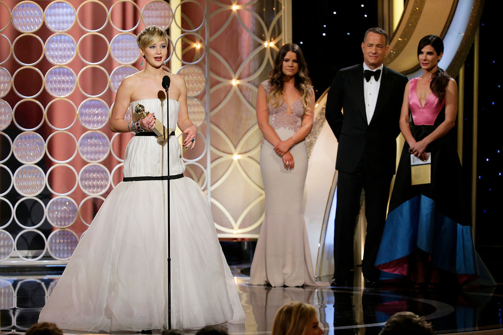 """. Jennifer Lawrence, left, accepts the award for best supporting actress in a motion picture for her role in \""""American Hustle,\"""" as presenters Sandra Bullock, right, and Tom Hanks, second right, look on during the 71st annual Golden Globe Awards at the Beverly Hilton Hotel on Sunday, Jan. 12, 2014, in Beverly Hills, Calif. (AP Photo/NBC, Paul Drinkwater)"""