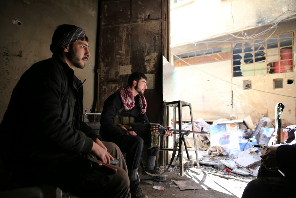Description of . Free Syrian Army fighters carry their weapons as they sit on guard in the Arabeen neigbourhood of Damascus, February 12, 2013. REUTERS/Mohammed Abdullah