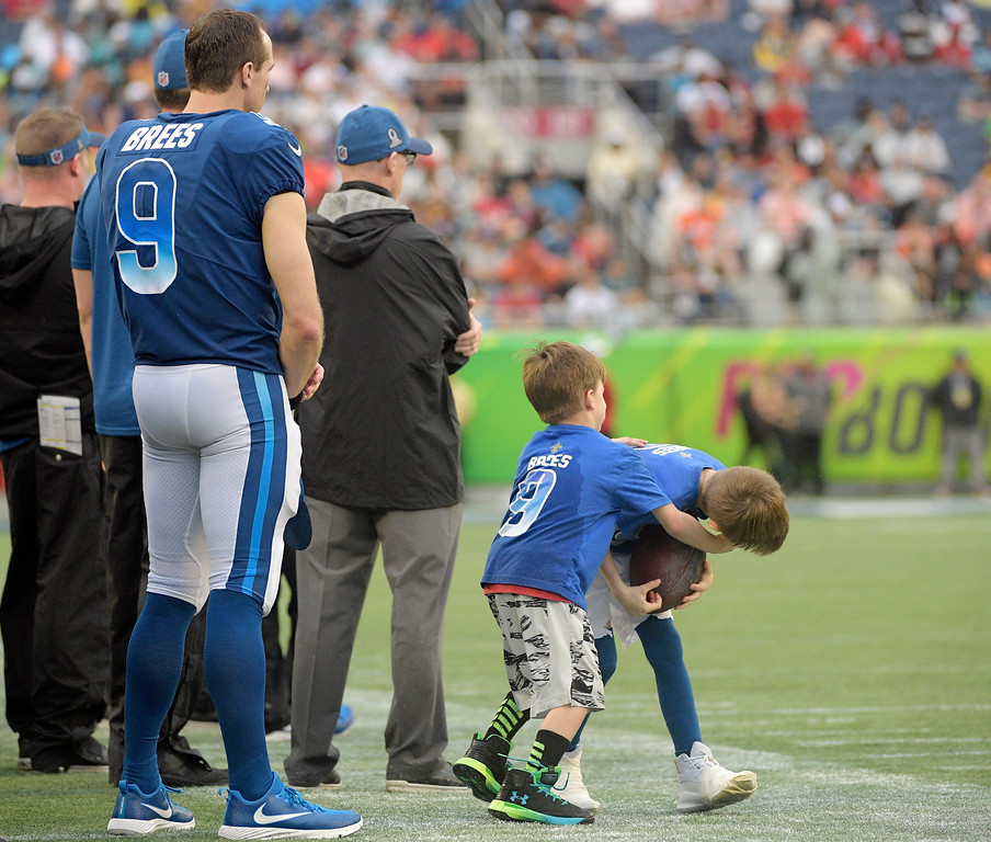 . NFC quarterback Drew Brees (9), of the New Orleans Saints, watches the game as his sons play on the sidelines, during the second half of the NFL Pro Bowl football game against the AFC, Sunday, Jan. 28, 2018, in Orlando, Fla. (AP Photo/Phelan M Ebenhack)