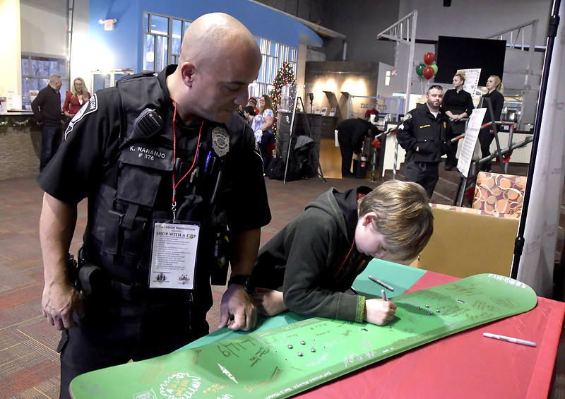 12/7/2017 Mike Orazzi   Staff Southington police officer Kevin Naranjo as Jared Beers signs a snowboard during a meet and greet held at Crystal Bees in Southington before shopping for Shop with a Cop, a one on one shopping experience pairing underprivileged children with law enforcement.