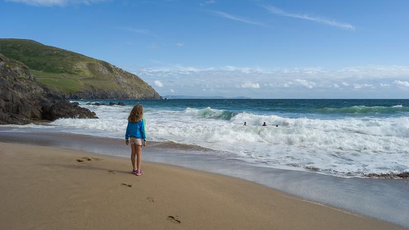 Girl watching family enjoying the waves of the ocean, Ballyferriter, County Kerry, Ireland