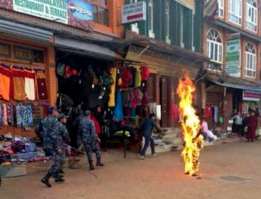 Description of . Nepalese policemen rush as a Tibetan monk burns after he set himself on fire in Katmandu, Nepal, Wednesday, Feb. 13, 2013. The Tibetan monk doused himself with gasoline and set himself on fire in Nepal's capital Wednesday in what is believed to be the latest self-immolation to protest Chinese rule in Tibet. Nearly 100 Tibetan monks, nuns and lay people have set themselves on fire in various countries, mostly in ethnic Tibetan areas inside China, since 2009.( AP Photo)