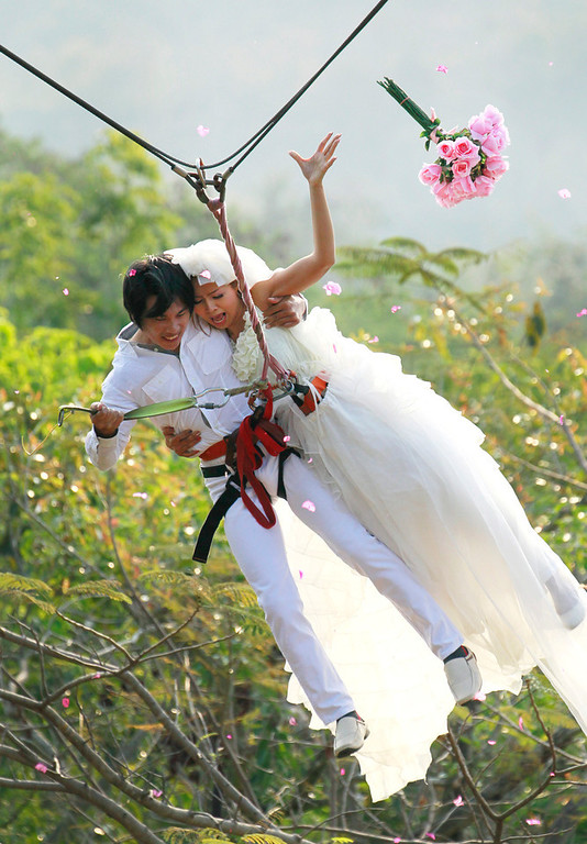 . Sopon Tapoatong, left, and his bride Chutuma Tapoatong swing out on a rappelling rope as part of an adventure themed wedding ceremony in Prachinburi province, Thailand, Wednesday, Feb. 13, 2012, on the eve of Valentine\'s Day. (AP Photo/Wason Wanichakorn)