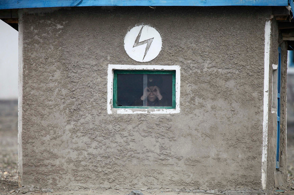 ". A North Korean soldier looks out of the window of a guard tower, on the banks of Yalu River, about 100 km (62 miles) from the North Korean town of Sinuiju, opposite the Chinese border city of Dandong, April 16, 2013. North Korea issued new threats against South Korea on Tuesday, vowing ""sledge-hammer blows\"" of retaliation if South Korea did not apologise for anti-North Korean protests the previous day when the North was celebrating the birth of its founding leader. REUTERS/Jacky Chen"