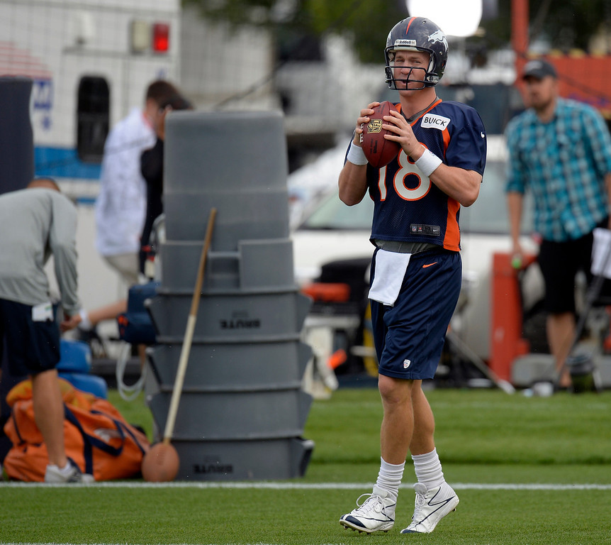 . Denver Broncos quarterback  Peyton Manning (18) starts off the day with a few throws during opening day of training camp July 25, 2013 at Dove Valley. (Photo By John Leyba/The Denver Post)