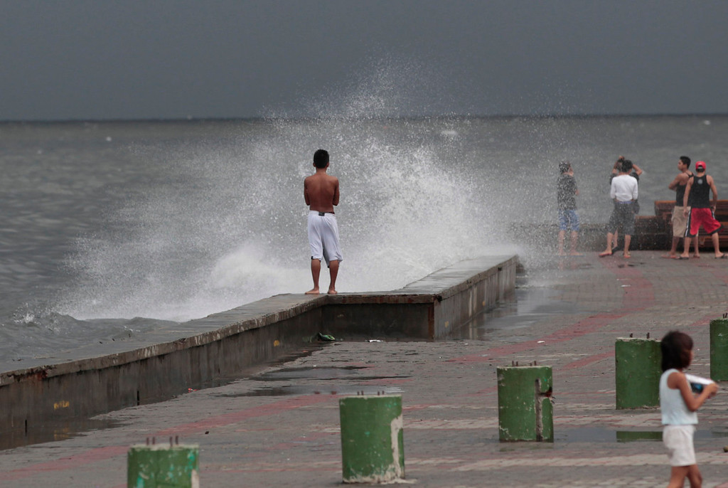 . A Filipino boy stands as waves hit a wall at a park in Navotas, north of Manila, Philippines on Monday, Aug. 12, 2013. Powerful Typhoon Utor battered the northern Philippines on Monday, toppling power lines and dumping heavy rains across mountains, cities and food-growing plain. The storm killed at least one man in a landslide and left 45 fishermen missing. (AP Photo/Aaron Favila)