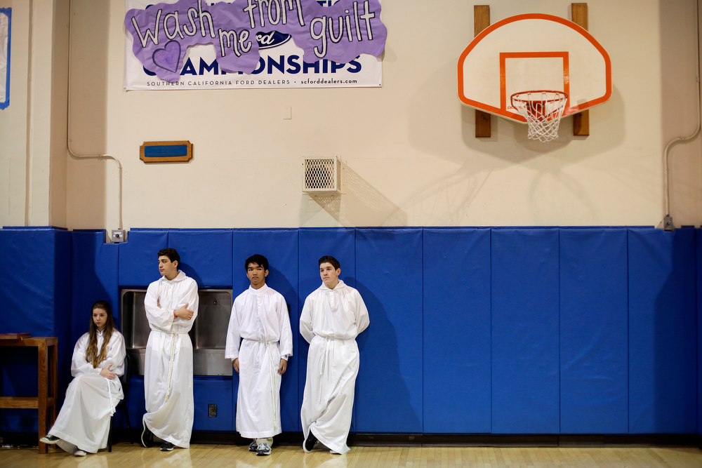 . Altar boys and an altar girl wait for the start of an Ash Wednesday Mass at Santa Margarita Catholic High School on Wednesday, March 5, 2014, in Rancho Santa Margarita, Calif. Ash Wednesday marks the beginning of Lent, a time when Christians commit to acts of penitence and prayer in preparation for Easter Sunday. (AP Photo/Jae C. Hong)