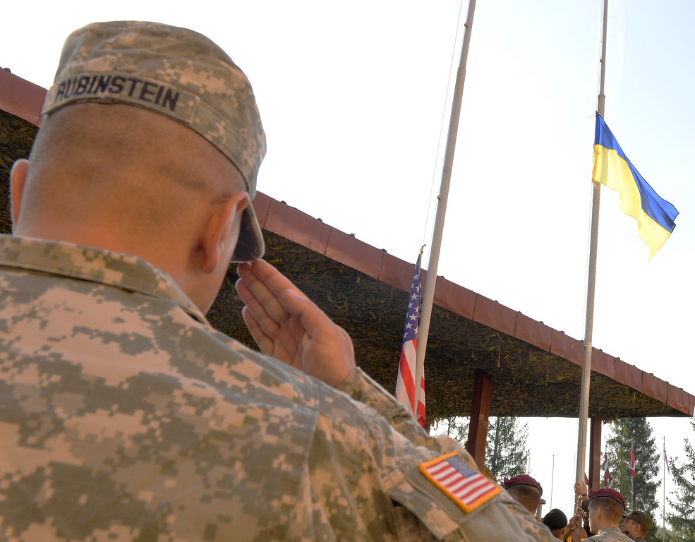 ". A serviceman of US Army salutes the raising a Ukrainian flag during the opening ceremony of the ""Rapid Trident\"" military exercises on September 15, 2014 near the western Ukrainian town of Yavoriv. US-led military exercises began in Ukraine on Monday after a day of deadly fighting between government forces and pro-Russian rebels in the restive east that has piled pressure on a shaky 10-day-old truce. AFP PHOTO/YURKO DYACHYSHYN/AFP/Getty Images"