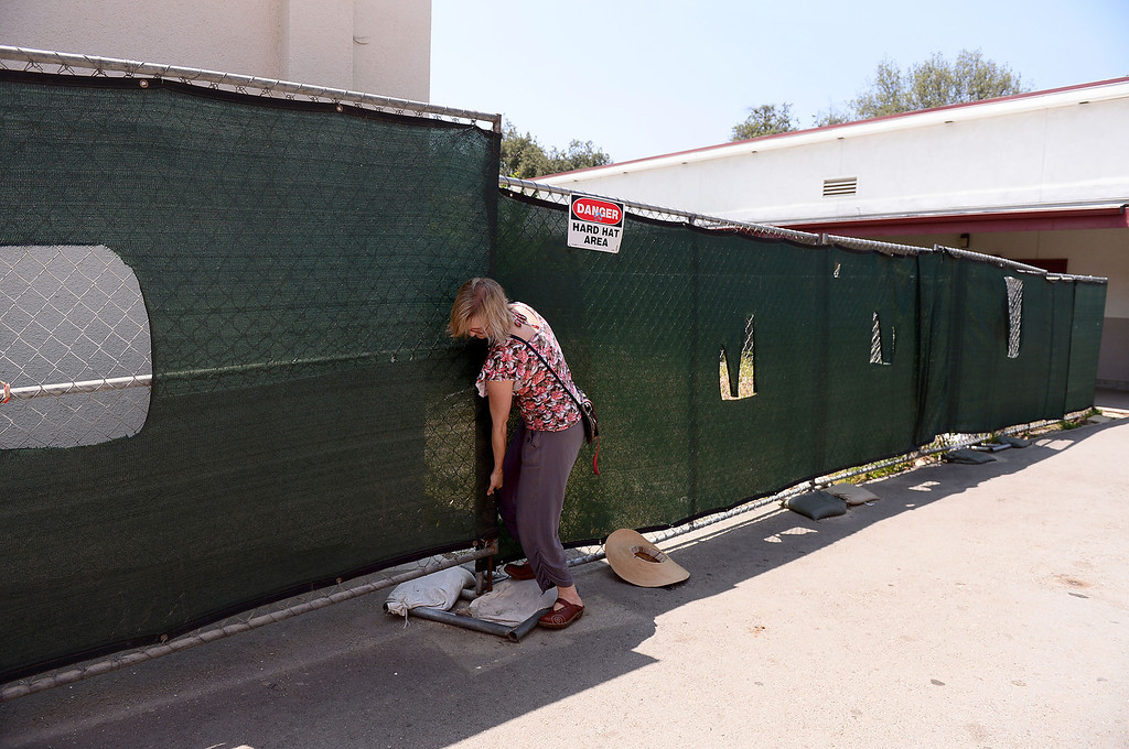 . Biology teacher Joan Stevens, who is trying to save the permaculture garden she cultivated at Arcadia High School from becoming concrete planter boxes as the school modernizes, leaves the garden area Thursday, June 13, 2013 though a construction fence. Stevens is working with district officials to turn the garden into an outdoor classroom.   (SGVN/Staff Photo by Sarah Reingewirtz)