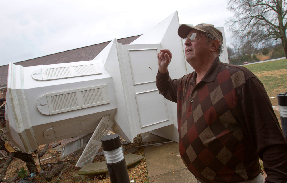 Description of . James Godsey, an elder at the First Cumberland Presbyterian Church in Rogersville, Ala., talks about the damage to the roof as he walks around the church steeple that was blown off the building by the storm  that roared across the Tennessee Valley over night. The church had water damage inside as well.(AP Photo/TimesDaily,Matt McKean)