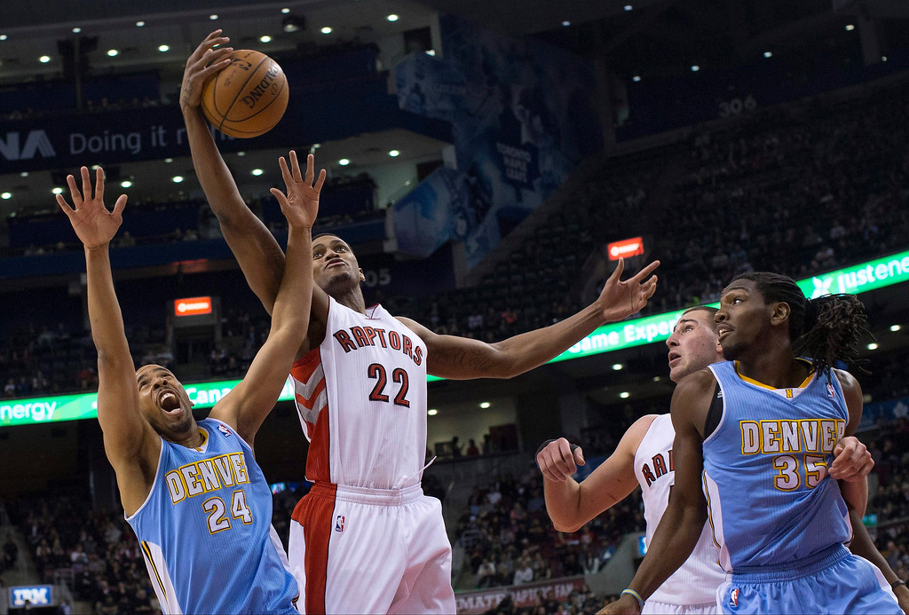 . Toronto Raptors\' Rudy Gay (22) gets to a rebound in front of Denver Nuggets\' Andre Miller, left, as Raptors\' Jonas Valanciunas, center right, and Nuggets\' Kenneth Faried watch during the first half of an NBA basketball game in Toronto on Tuesday, Feb. 12, 2013. (AP Photo/The Canadian Press, Chris Young)