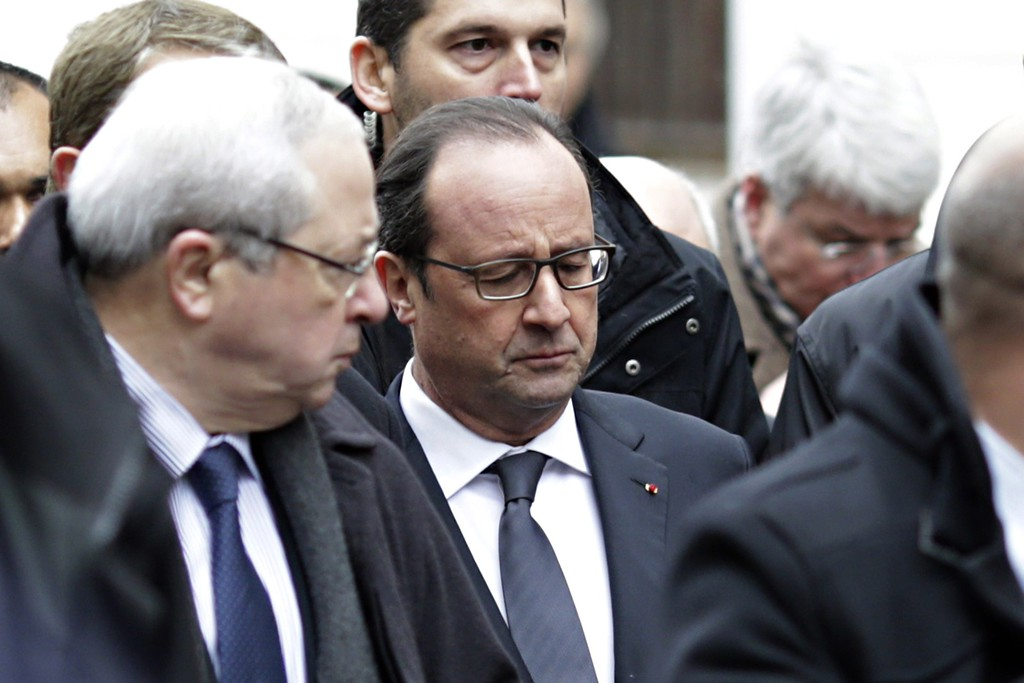 . French President Francois Hollande (C) arrives at the headquarters of the French satirical newspaper Charlie Hebdo in Paris on January 7, 2015, after armed gunmen stormed the offices leaving eleven dead, including two police officers, according to sources close to the investigation.   AFP PHOTO / KENZO  TRIBOUILLARD/AFP/Getty Images