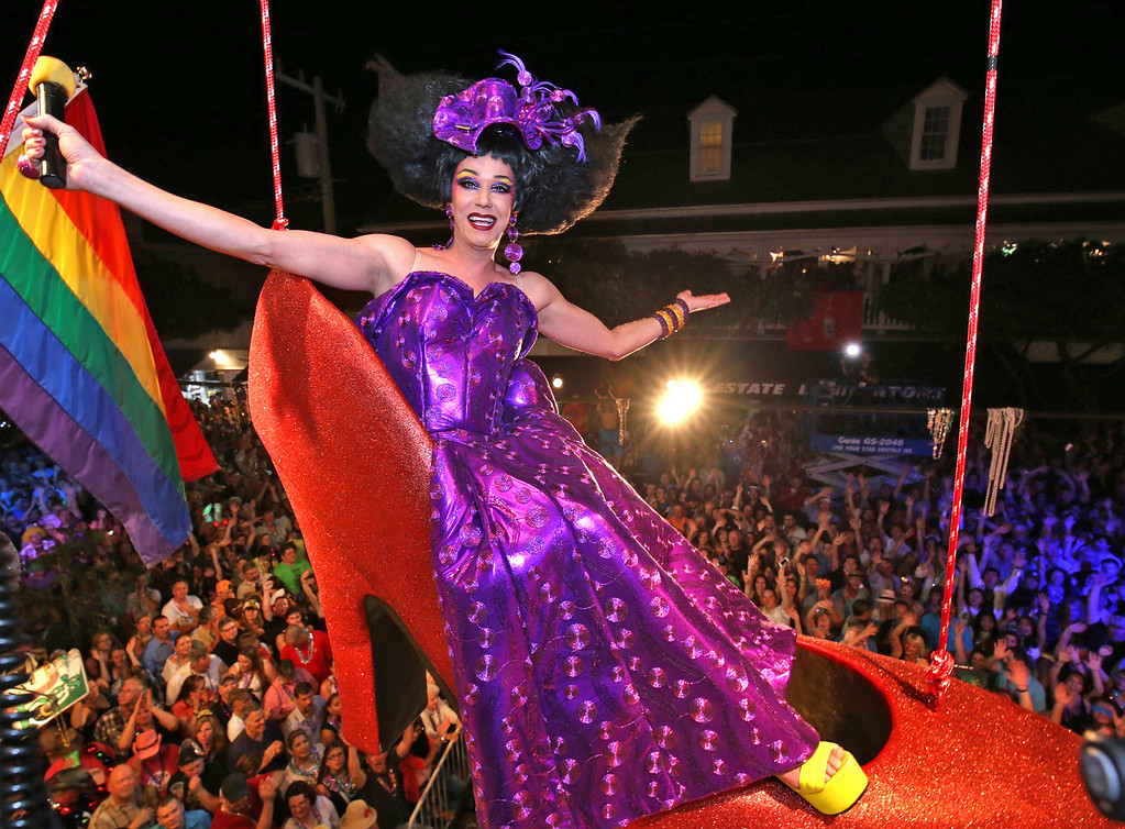 """. \""""Sushi,\"""" portrayed by female impersonator Gary Marion, hangs in a giant replica of a woman\'s red high heel over Duval Street, late Wednesday, Dec. 31, 2014, at the Bourbon Street Pub in Key West, Fla. The Red Shoe Drop is a Key West New Year\'s Eve tradition and is one of four Florida Keys warm-weather takeoffs on New York City\'s ball drop marking the beginning of the new year. (AP Photo/The Key West Citizen, Rob O\'Neal) MIAMI HERALD OUT"""