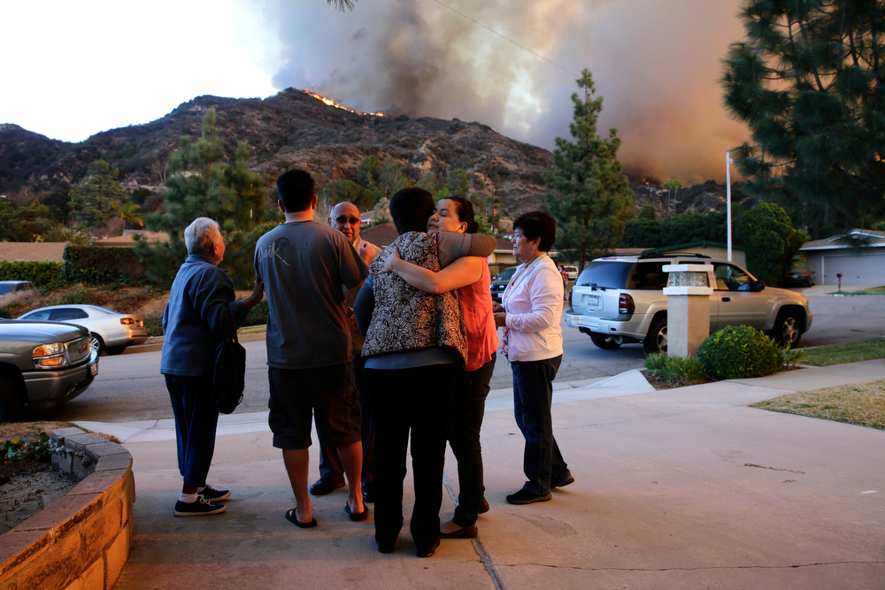 . Family members comfort each other as they evacuate their home as firefighters battle a wildfire, Thursday, Jan. 16, 2014, in Azusa, Calif. A wildfire burned out of control near homes in the dangerously dry foothills of the San Gabriel Mountains early Thursday, fanned by gusty Santa Ana winds that spit embers into neighborhoods in the city below, igniting trees. Evacuations were ordered for houses at the edge of the fire. (AP Photo/Jae C. Hong)