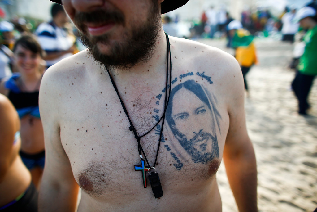 ". A pilgrim from Argentina on Copacabana beach has a Jesus tattoo that reads in Spanish ""How is it that they don\'t speak about you if your voice burns inside me\"" as he waits with others for Pope Francis\' arrival in Rio de Janeiro, Brazil, Saturday, July 27, 2013. Francis will preside over an evening vigil service on Copacabana beach that is expected to draw more than 1 million young people. (AP Photo/Victor R. Caivano)"