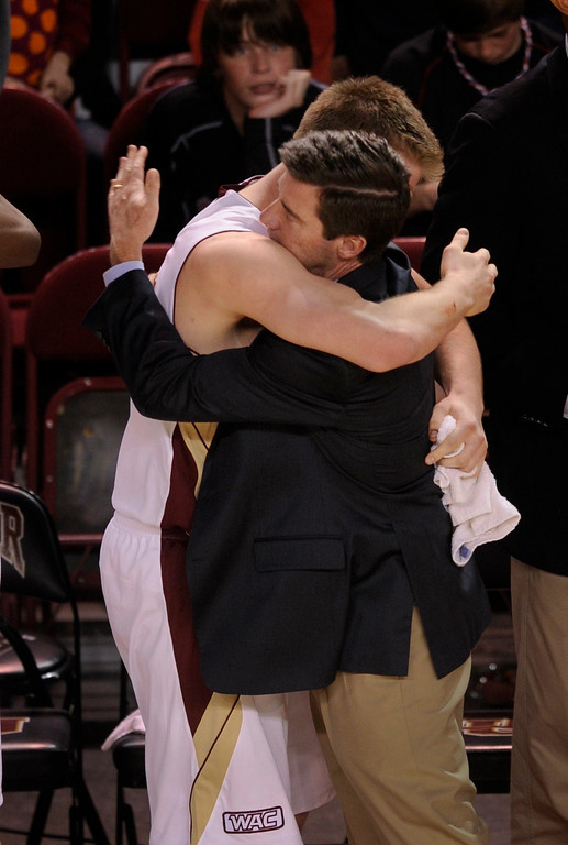 . Denver coach Joe Scott embraced senior Chase Hallam in the closing minute of the game. The University of Denver men\'s basketball team defeated the Louisiana Tech Bulldogs 78-54 at Magness Arena Saturday night, March 9, 2013. (Photo By Karl Gehring/The Denver Post)
