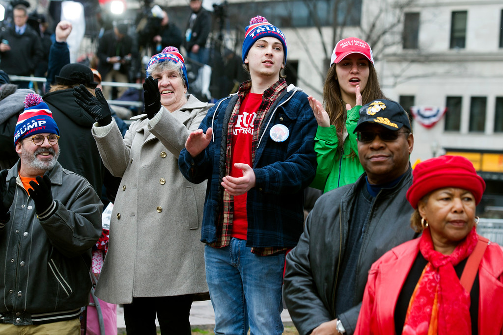 . President Donald Trump supporters, on Pennsylvania Avenue, applaud as Trump is sworn-in to office in Washington, Friday, Jan. 20, 2017. (AP Photo/Cliff Owen)