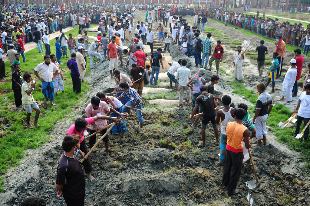 . Bangladeshis bury the remains of garment workers killed in the garment factory collapse at a graveyard in Dhaka on May 1, 2013. AFP PHOTO/Munir uz  ZAMAN/AFP/Getty Images