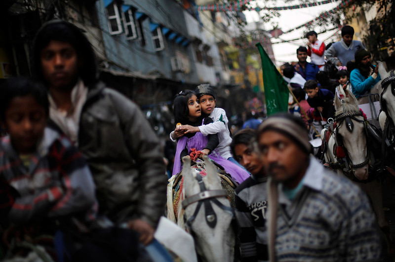 . Indian Muslim children ride a horse as they take part in a Eid-e-Milad procession marking the birth anniversary of the Prophet Muhammad, in New Delhi, India, Tuesday, Jan. 14, 2014. Some thousands of people gather along the streets to chant religious slogans during the annual Eid-e-Milad festival marking the anniversary of Prophet Muhammad\'s birth. (AP Photo/Altaf Qadri)
