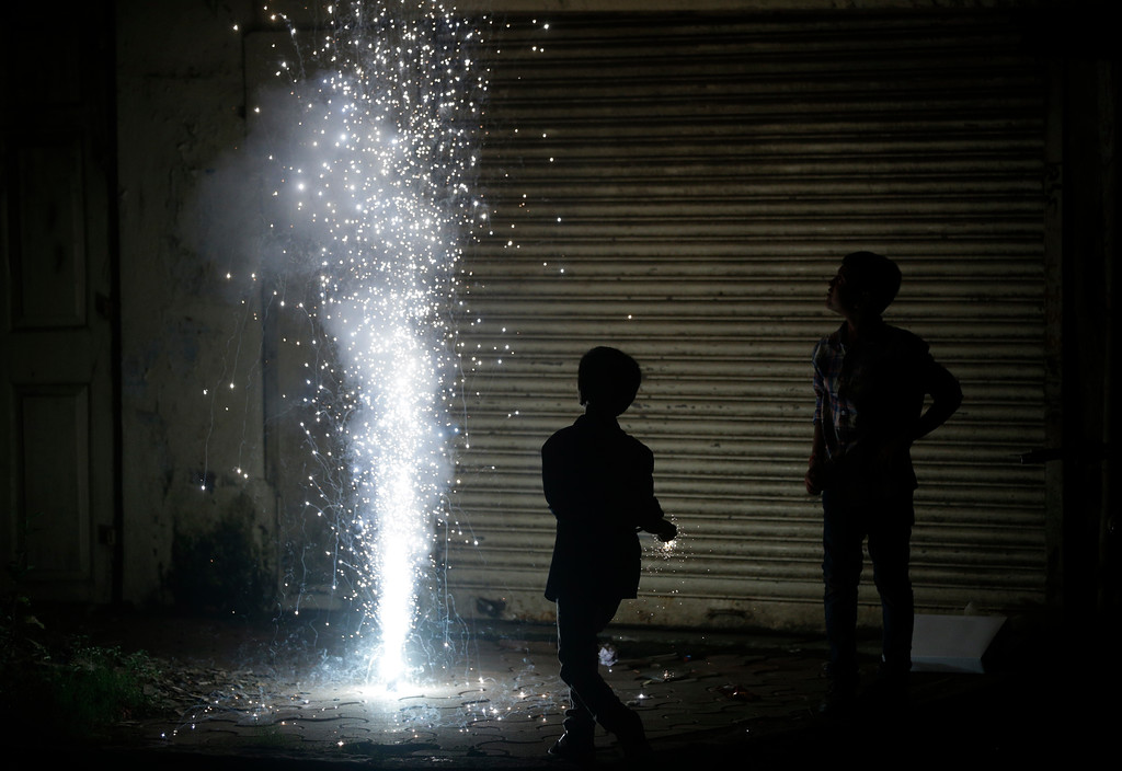 . Children light firecrackers to celebrate Diwali, the Hindu festival of lights, in Mumbai India, Thursday, Oct. 19, 2017. (AP Photo/Rafiq Maqbool)