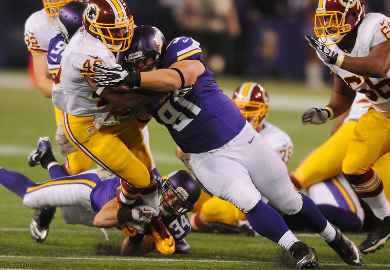 . Minnesota defensive tackle Chase Baker and free safety Andrew Sendejo combine to bring down Washington running back Alfred Morris in the first quarter. (Pioneer Press: John Autey)