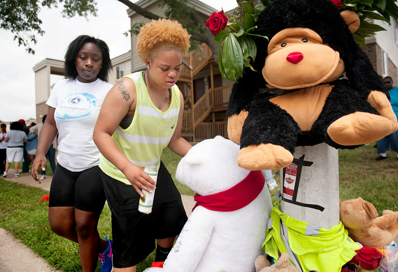 . Amiah Murry, left, and Sabrina Webb add items to a spontaneous memorial for shooting victim Michael Brown, 18, Sunday, Aug. 10, 2014 at the scene of the shooting in Ferguson, Mo. Brown died following a confrontation with police, according to St. Louis County Police Chief Jon Belmar, who spoke at a press conference Sunday. (AP Photo/Sid Hastings)