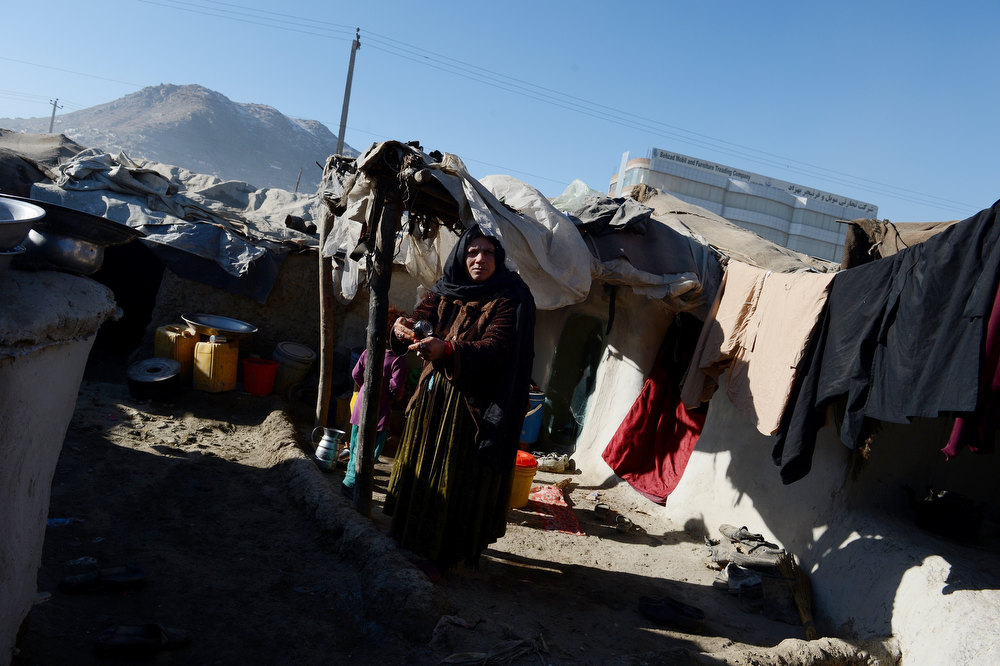 . An internally displaced Afghan woman stands outside her mud shelter in a makeshift camp as winter approaches  in Kabul on December 4, 2012. The country has nearly half a million displaced people, many living in primitive camps where the cold weather will mean uncertainty for some. SHAH MARAI/AFP/Getty Images